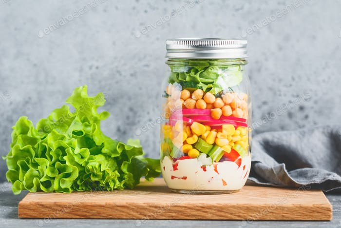 Single jar with layering vegan salad for healthy lunch. The concept of fitness and vegetarian food.