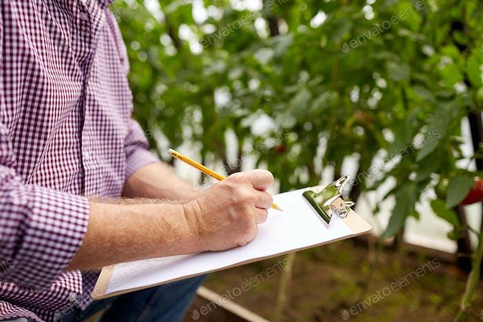 senior man writing to clipboard at farm greenhouse