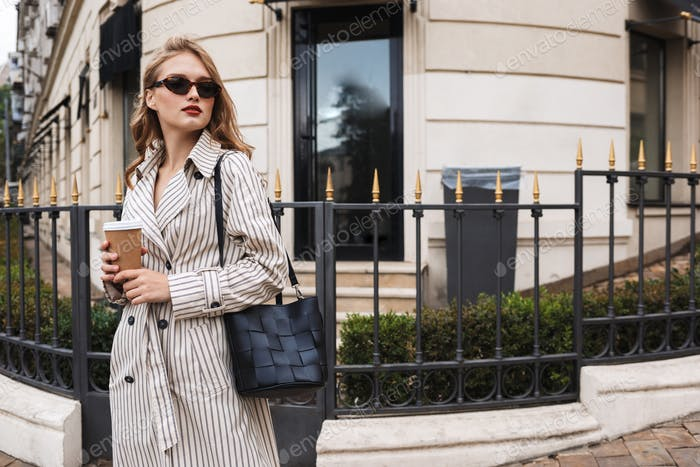 Beautiful girl in striped trench coat and sunglasses with black