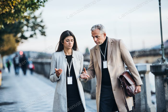 Man and woman business partners walking by a river in city of Prague, talking.