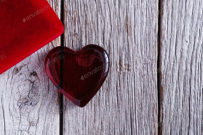 Red glass heart on grey wood background, valentine day