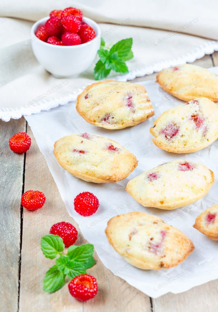 Madeleines cookie with raspberry on parchment paper