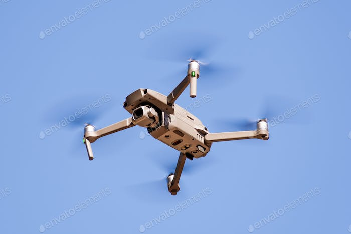 Close up of flying drone quad-copter with digital camera; blue sky background
