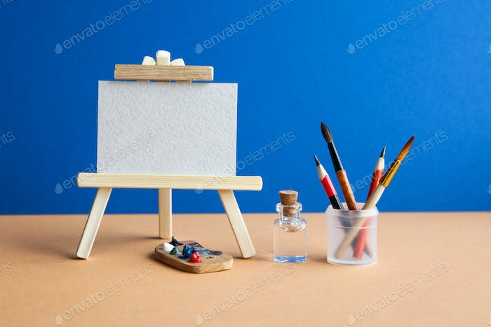 Wooden easel with textured blank paper canvas on blue brown background.