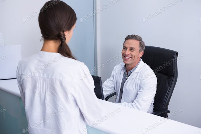 Happy dentist and woman talking in cabin