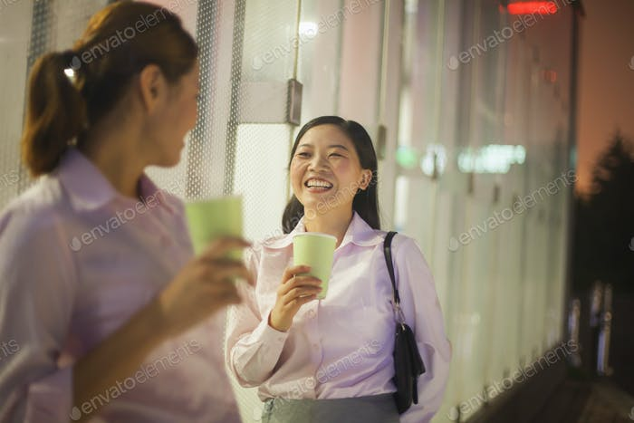 Young businesswomen smiling and drinking coffee outdoor
