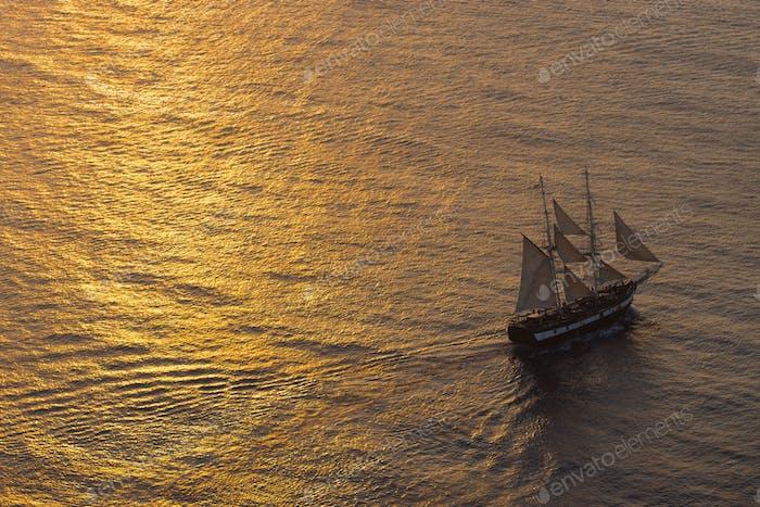 Ship sailing at sunset