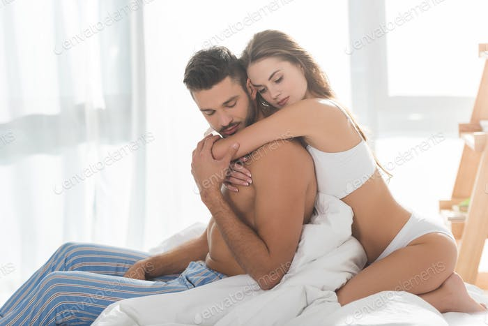 beautiful young woman embracing boyfriend from behind
