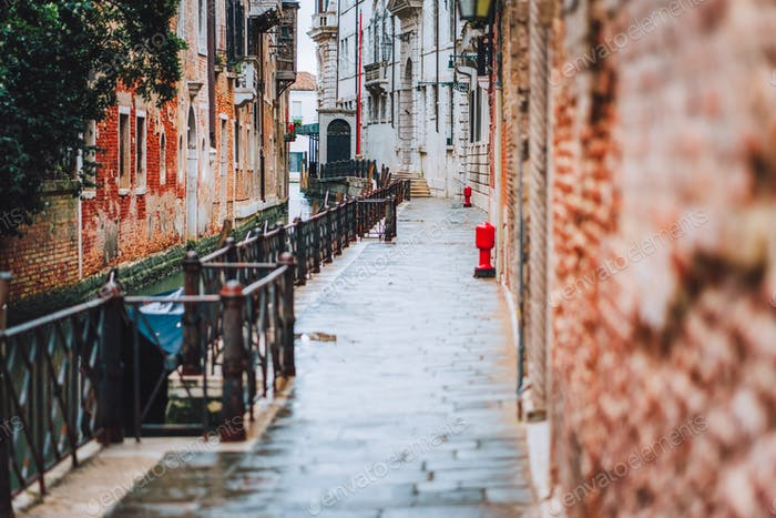 Venice, Italy. The small streets and narrow channel with colored brick houses on the shore of old