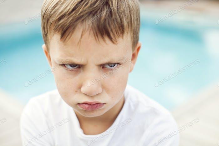 Primer plano de niño enojado contra la piscina