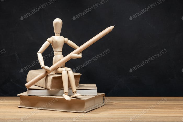 Wooden mannequin holding a pencil sitting on a pile of books.