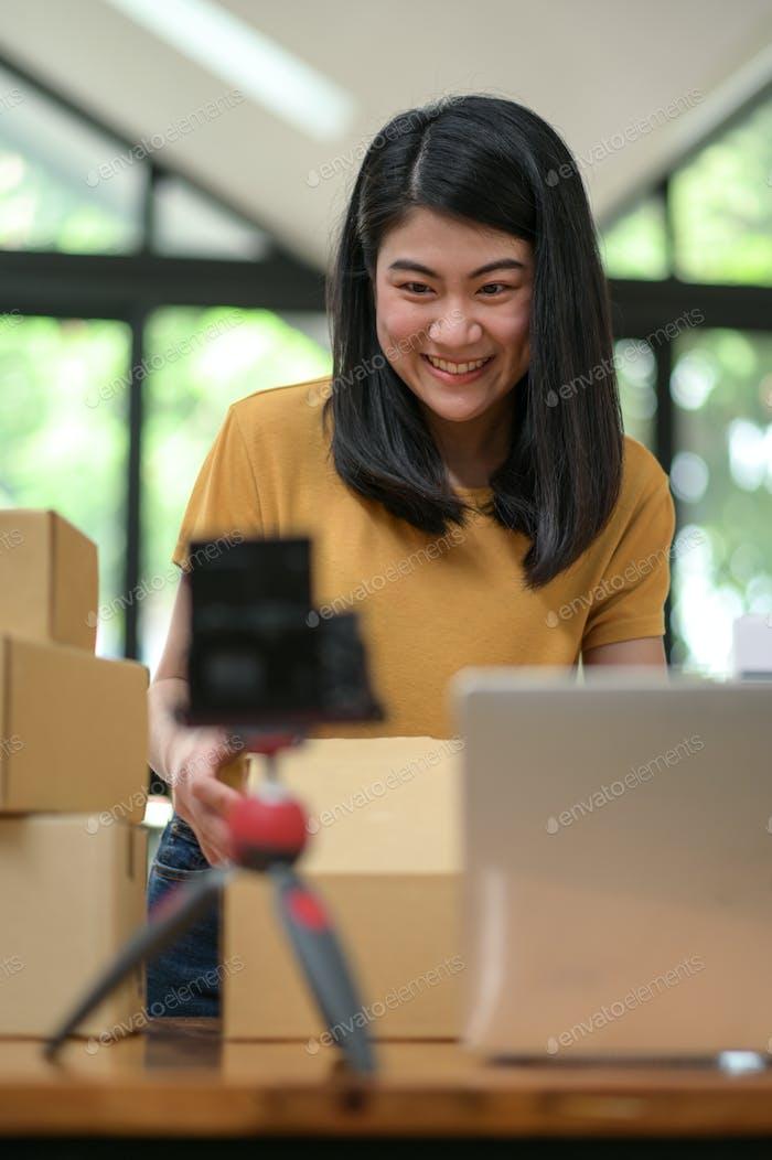 Una joven vive a través de la cámara para vender productos en línea, Vendiendo productos en línea.