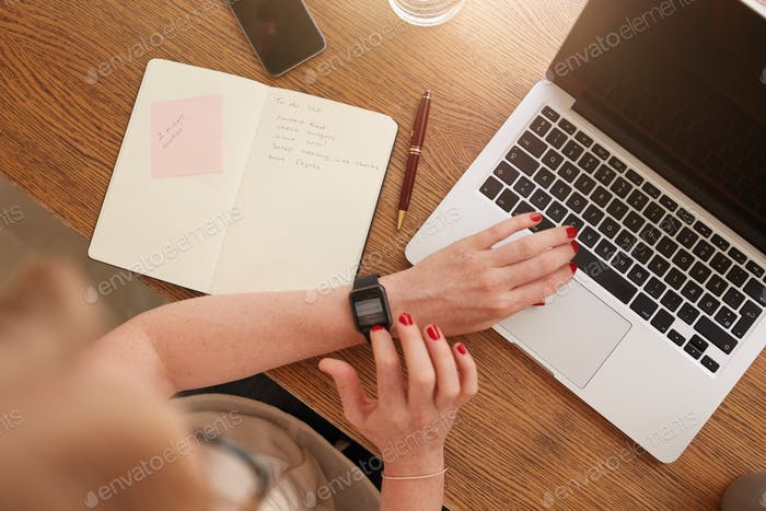 Woman sitting at her desk and using smartwatch