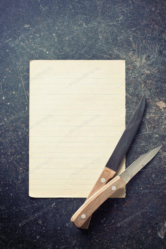 Blatt Papier mit Messern