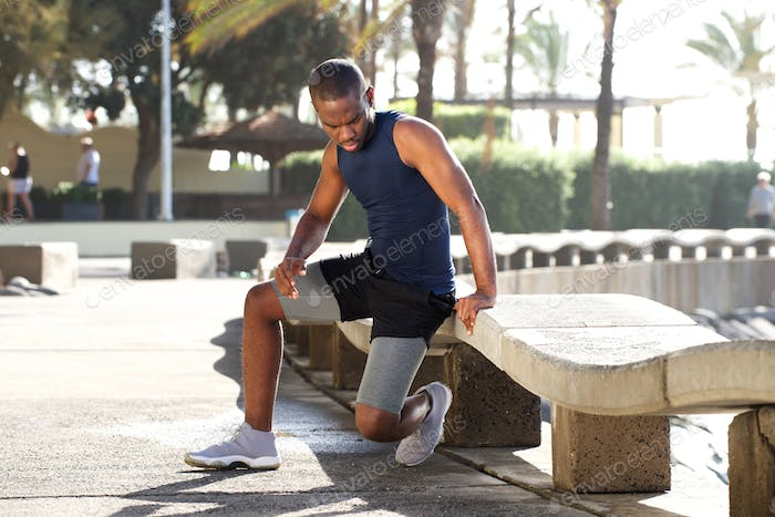 young active african american man doing exercise outdoors