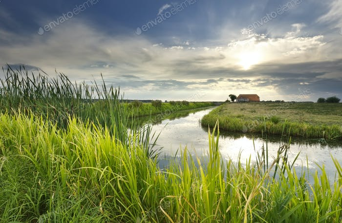 sunbeams over house, river and meadow
