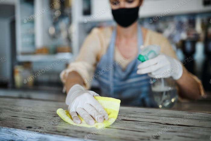 Coffee shop woman owner working with face mask and gloves , disinfecting counter