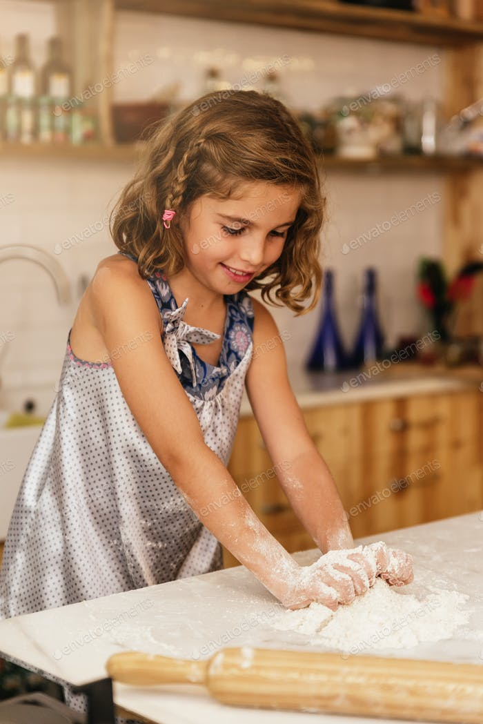 Little child girl kneading dough prepare for baking cookies.