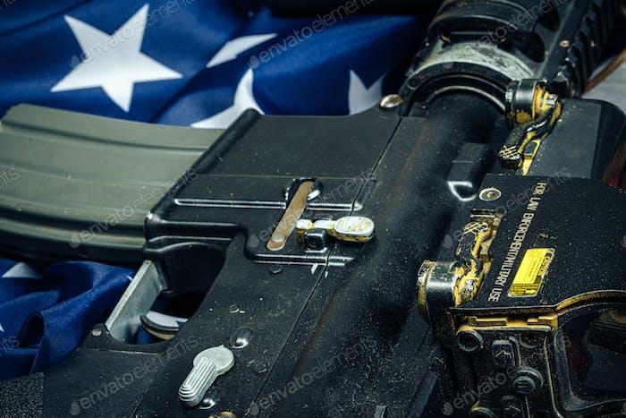 Bandera de batalla estadounidense y rifle de asalto en la mesa de madera