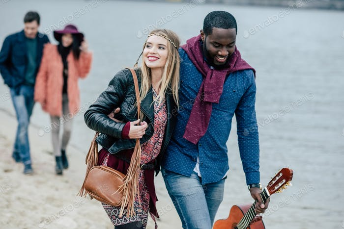 Young people having pleasant stroll on river beach. Smiling couple on foreground
