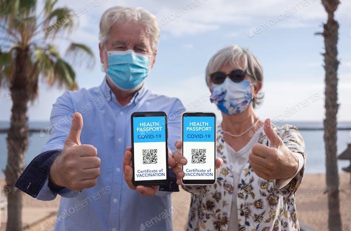Senior couple vaccinated against coronavirus contagion show health passport certificate