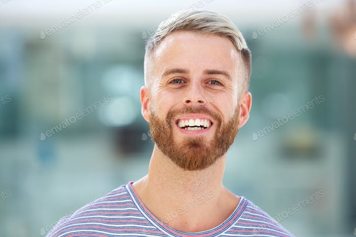 handsome young man with beard laughing
