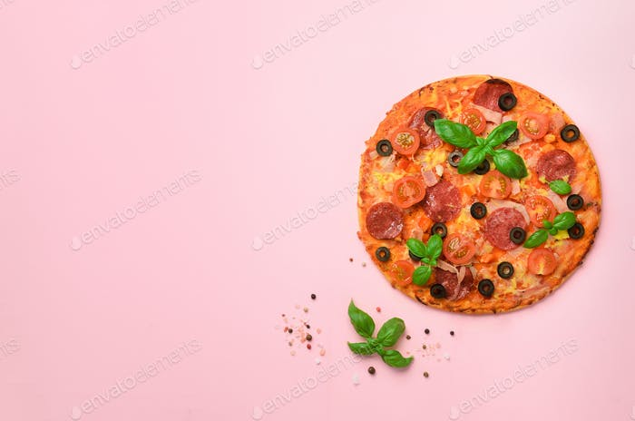 Delicious italian pizza, basil leaves, salt, pepper on pink background with copyspace. Top view