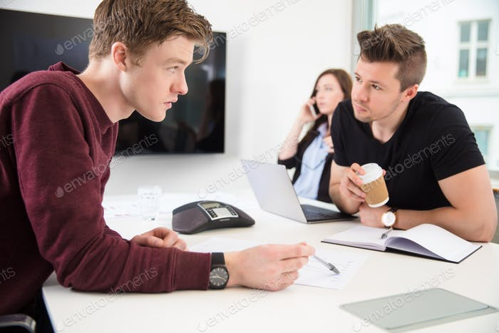 Businessmen Discussing While Colleague Using Smart Phone