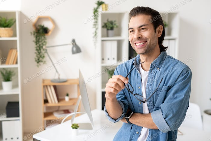 Happy young businessman with toothy smile standing by workplace