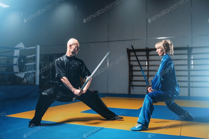 Wushu fighters, man and woman with swords