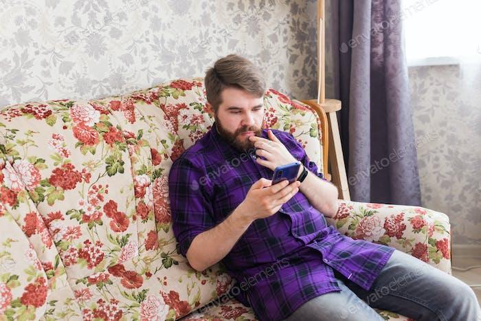 Hombre guapo enviando mensajes de texto con su smartphone en la sala de estar