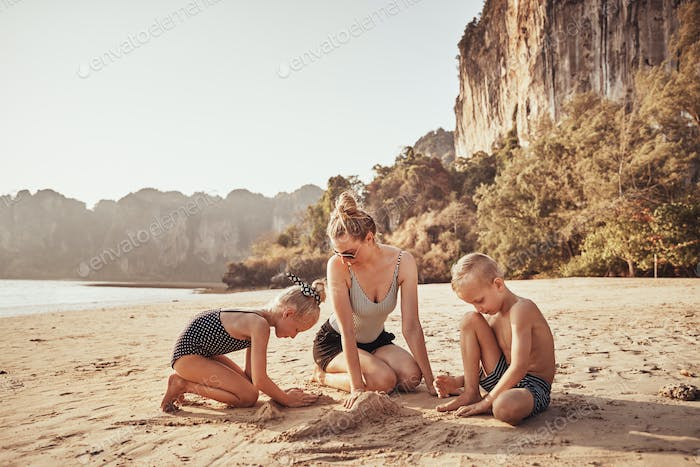 Mother and her adorable children playing on a sandy beach