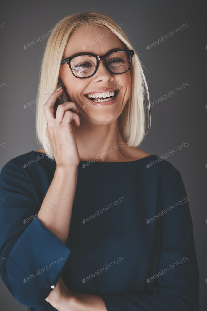 Laughing busineswoman talking on her cellphone against a gray background