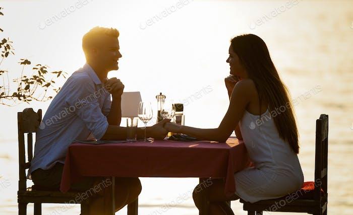 Пара обмен романтический ужин на закате на пляже