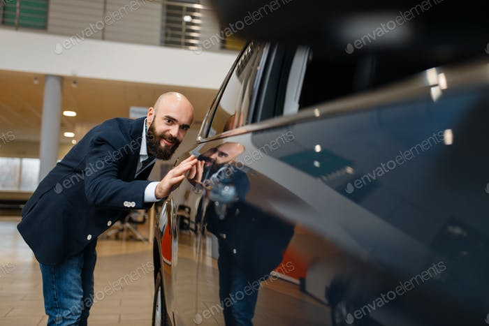 Man checks the paintwork of new automobile