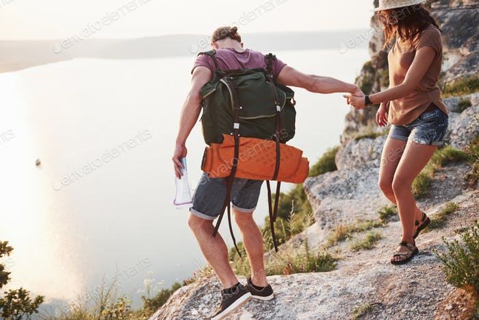 Two tourist male and woman with backpacks climb to the top of the mountain and enjoying sunrise