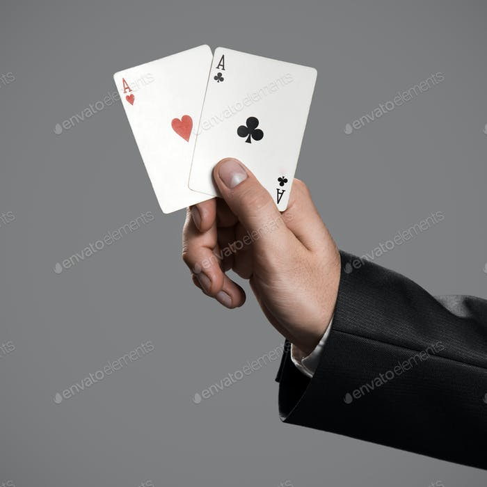 A Businessman Holding An Aces On Gray Background.