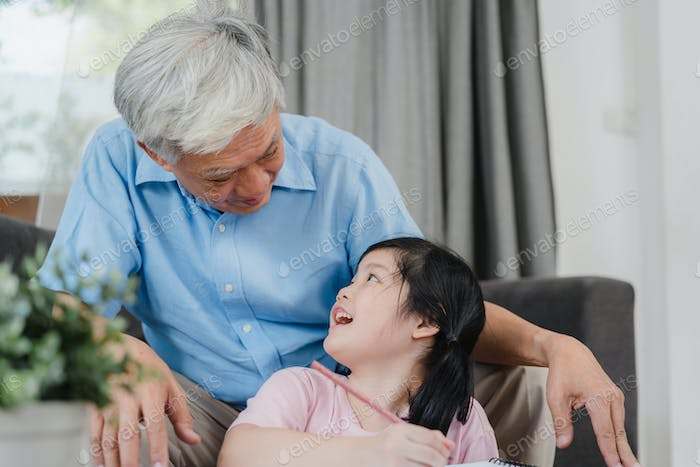 Asian grandfather teach granddaughter drawing and doing homework at home.