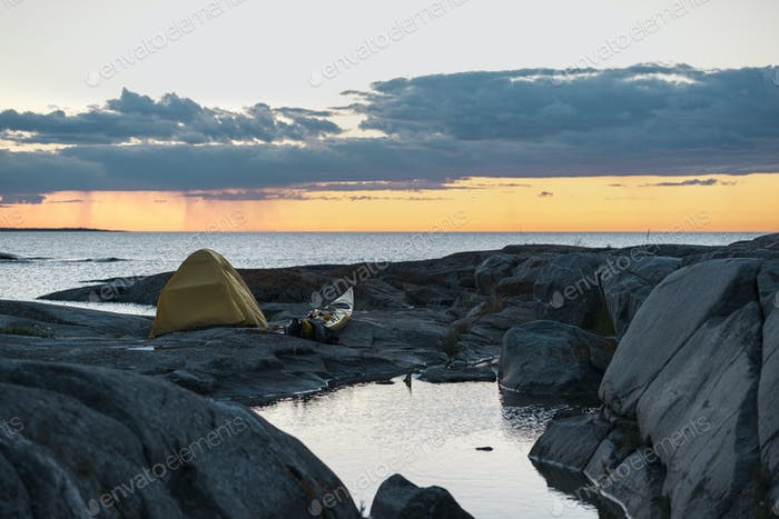 Tent on rocky beach at sunset
