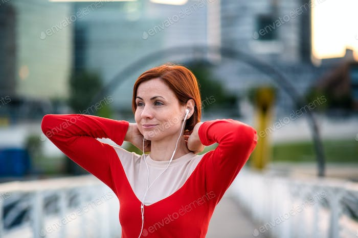 Front view of young woman runner with earphones in city, resting
