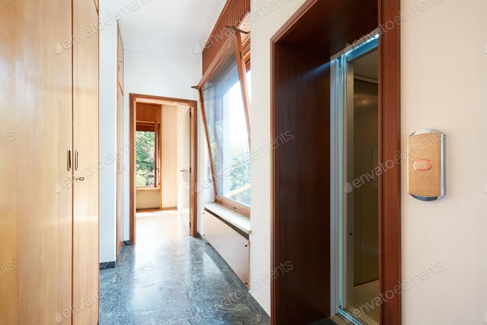 Corridor with wooden wardrobe, window and elevator door