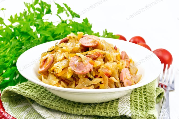 Cabbage stew with sausages in white plate on table