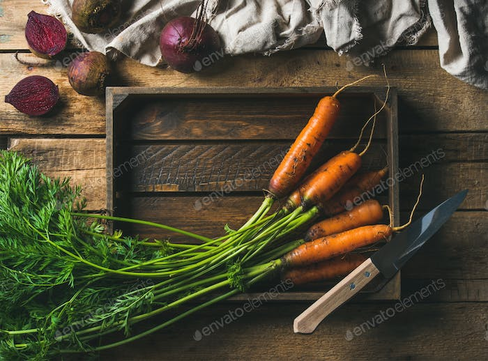 Fresh carrots and beetroots in wooden tray over rustic background