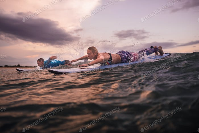 Surfers man and girl are floating on board