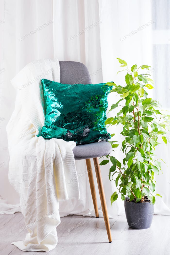White plaid and green sequins pillow with flower pot on gray armchair over window of living room