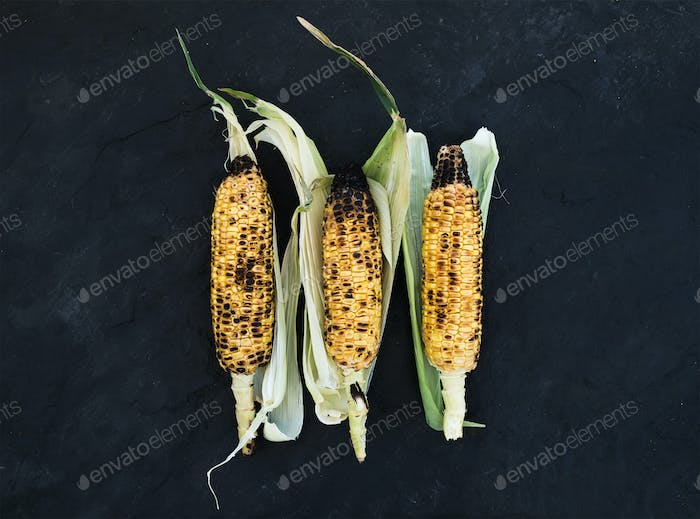 Grilled corn over black slate stone background, top view.