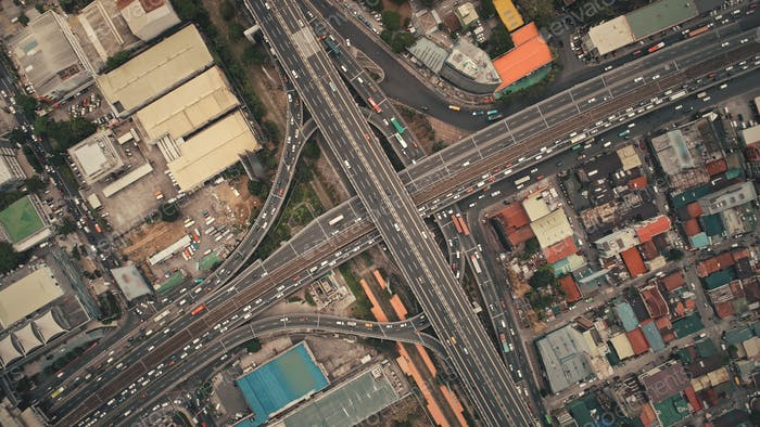 Top down of cross road traffic with cars, trucks, vehicles in aerial view. Downtown of Manila city