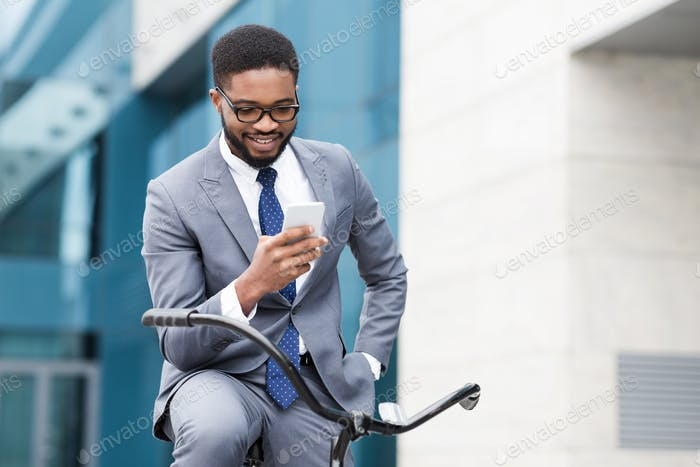 Happy afro businessman using smartphone, riding on bicycle