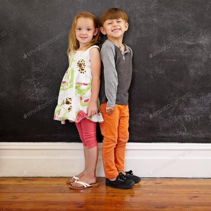 Little kids standing in front of blackboard
