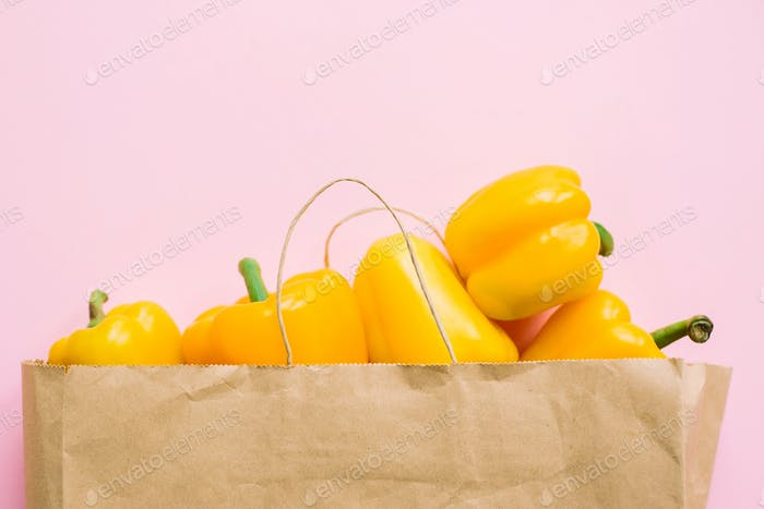 Bell peppers in paper bag on pink background